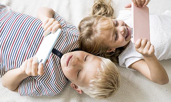 Zwei Kinder schauen auf Tablets